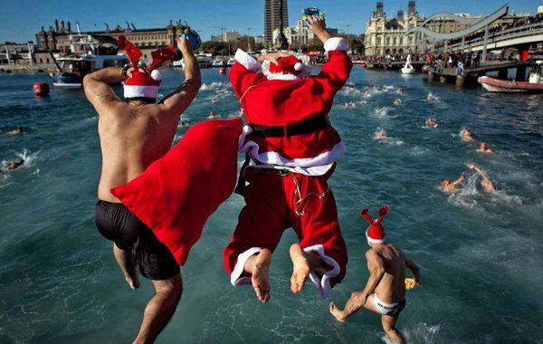 Merry Manly Christmas. Spanish men swim in the cold waters off Barcelona.