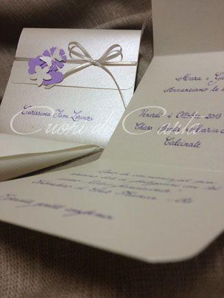 Partecipazione scritta a mano, carta perlata, chiusa con nastro in raso e dettagli in carta martellata e perlata. Personalizzabile nei colori.