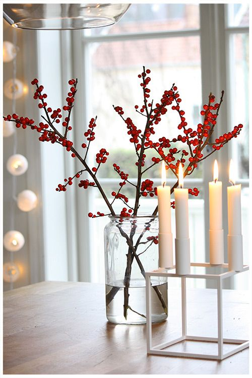A minimal look for a modern thanksgiving or Christmas. White lights, By  Lassen candleholder and simple vase with twigs with red berries.