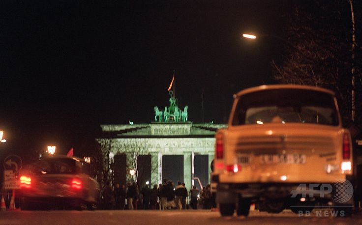 """East German cars, in particular a Trabant (R), also known as the Trabi, or as the """"cardboard-box-on-wheels"""", the car which symbolised communist East Germany, wait at Unter den Linden avenue in East Berlin the opening of the crossing point under the Brandenburg Gate (background) into West Berlin after the opening of the Berlin Wall on November 09, 1989. (c)AFP/PATRICK HERTZOG ▼1Nov2014AFP