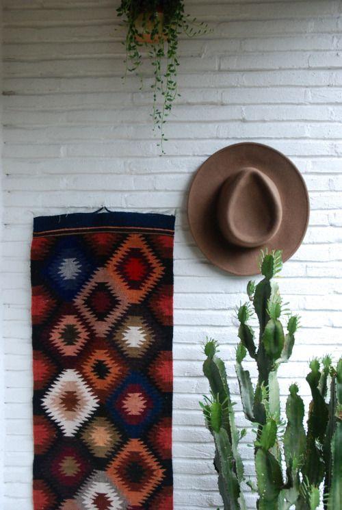 Brick wall, Mexican blanked, wall carpet, hang plants, cactus