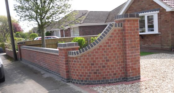 Front wall design curved with grey coping stones garden for Designs for brick garden walls