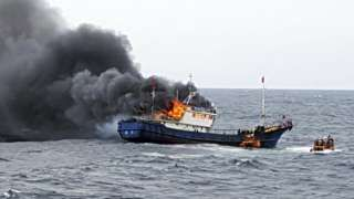"""Image copyright                  South korean Mokpo Coast Guard                                                     Three Chinese fisherman have died in a fire after their boat was boarded by the South Korean coastguard. The men, who were suspected of illegal fishing, were caught in the blaze after the coastguard officers threw a """"flashbang"""" or stun gr"""
