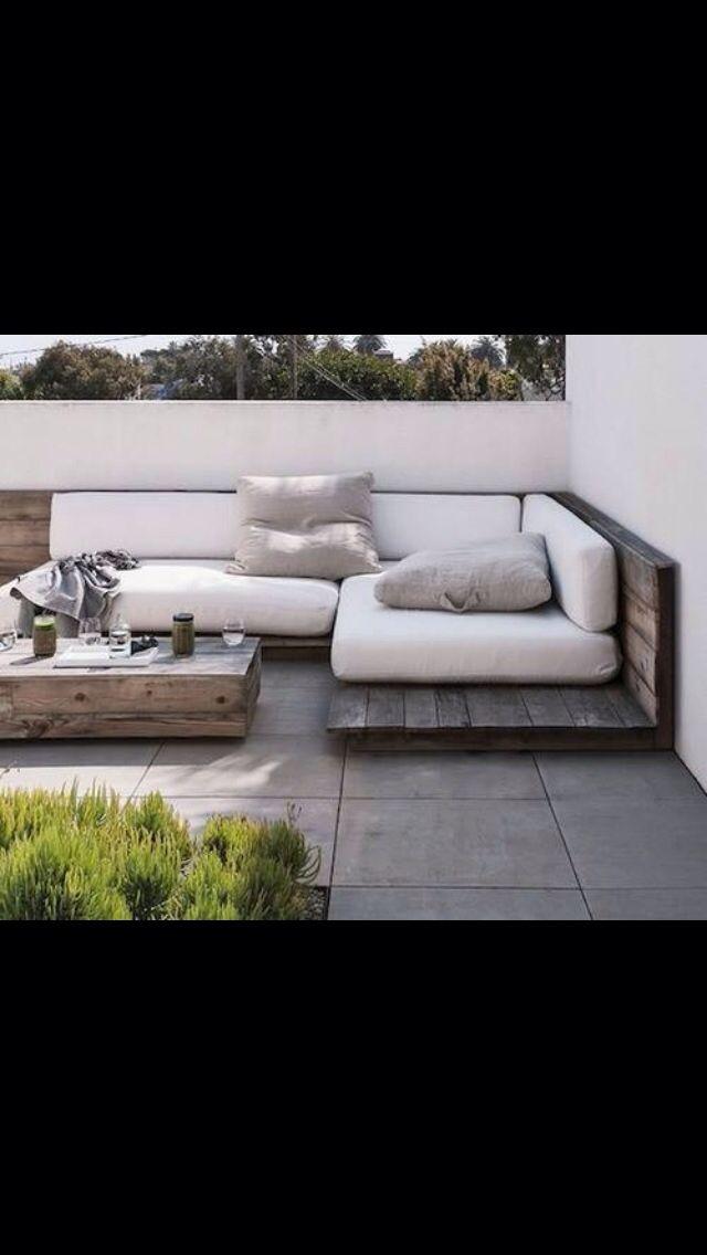 Lage loungebank van enkele laag houten planken met dikke kussens