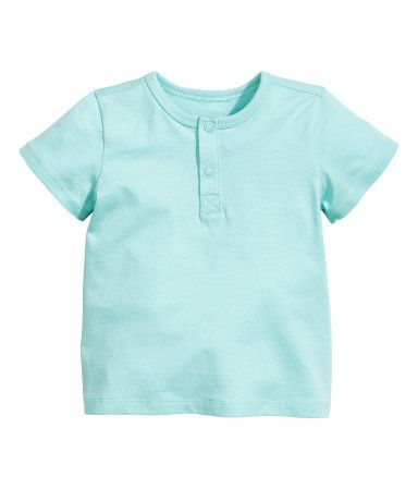 Mint green. CONSCIOUS. Short-sleeved henley shirt in organic cotton jersey with snap fasteners at front.
