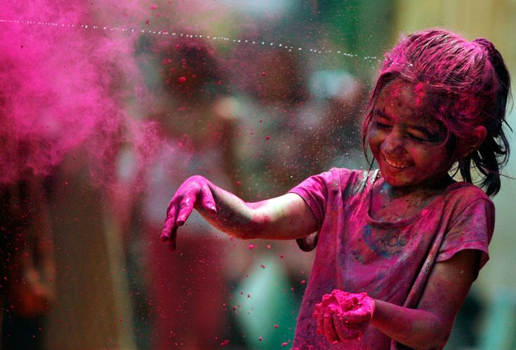 An Indian girl, her face smeared with colored powder, reacts as water is squirted on her during Holi celebrations in Chennai, India, on Marc...