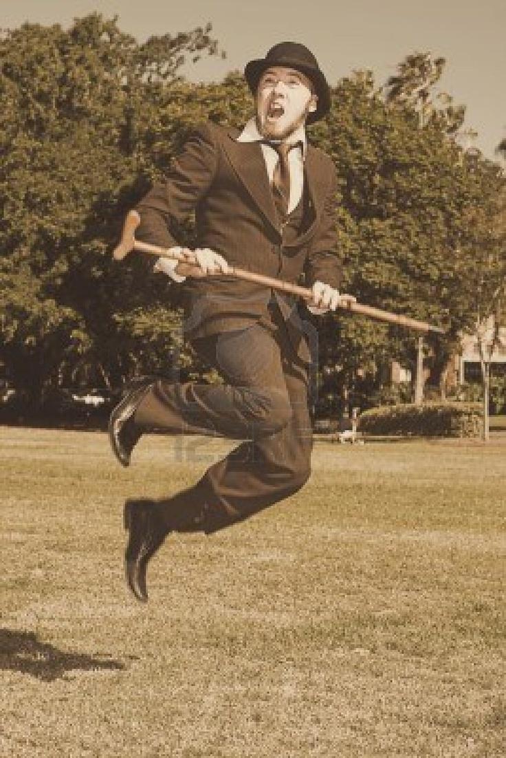 レトロなスーツ、山高帽や草の上を歩いてスティックジャンプ空中で幸せな若い男のセピア色の表示 ロイヤリティーフリーフォト、ピクチャー、画像、ストックフォトグラフィ. Image 13453522.