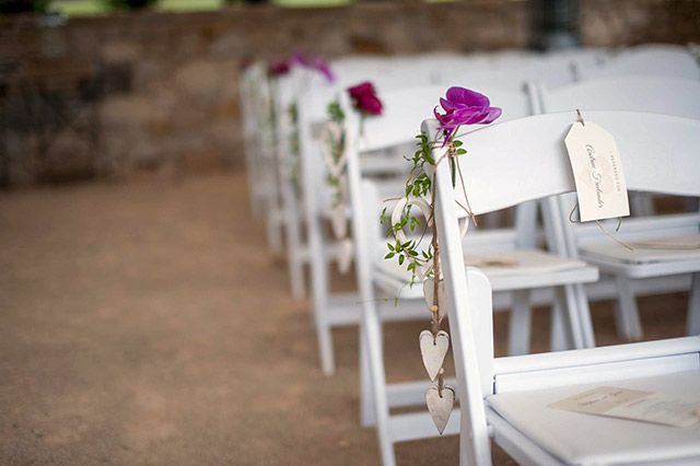 Single flowers decorated the aisle chairs. Image: Solas Wedding & Portrait Photography