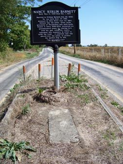 The grave of Nancy Barnett sits smack in the middle of Hill's Camp Road, a country road near a cornfield. Barnett had been dead more than 65 years when county officials decided to widen the road in 1901 and move the cemetery. In protest, Barnett's grandson, Daniel O. Doty, sat atop his grandma's grave with a shotgun. Eventually, they built the road around Barnett, and she rests there to this day....... I know that I would like Daniel Doty! Good for you Dan. Rest in peace Nancy.