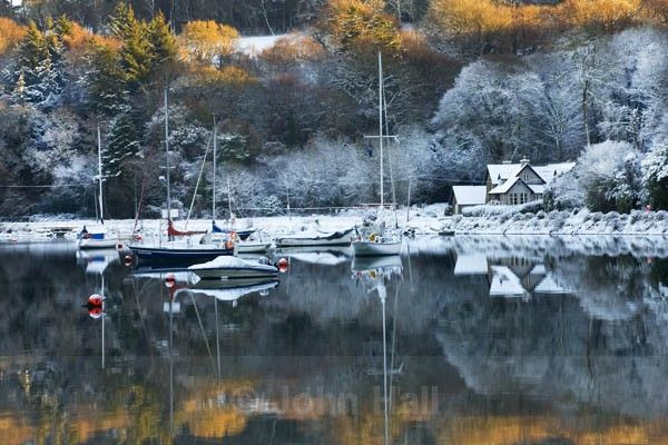 Winter reflections of a snow scene on the calm waters of Drakes Pool, near Crosshaven, County Cork, Ireland