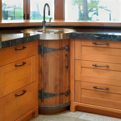 "The shape of the prep sink echoes the cylinder feature counter on the smaller island. Hanl chose a wider than standard Shaker door for the fir cabinetry, accenting with hand-scraped texture on the bar back. ""This gave me the heavy dimension and scale I was looking for to balance the sheer size of the room,"" she says."