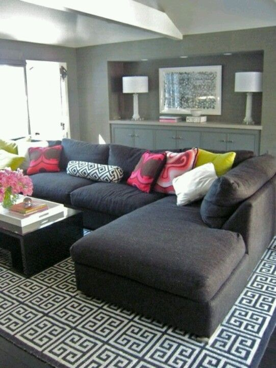 Simple black couch with pops of color in the pillows and flowers. I want THIS couch!!