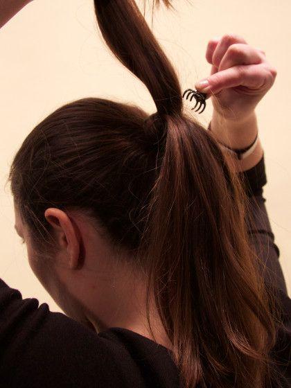 Schritt 5: Soll dein Pferdeschwanz noch bauschigeraussiehen. Kein Problem. Einfach vom oberen Teil des Zopfes eine dicke Haarsträhne abteilen, eine Klammer dichtam Haargummi festklemmen...