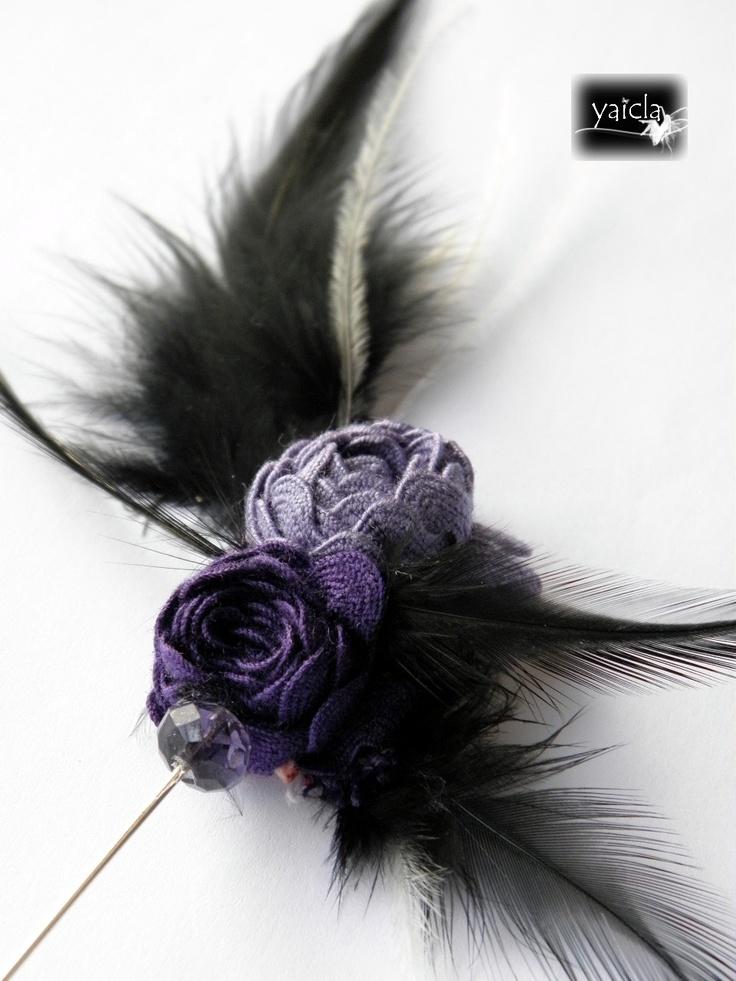 Alfiler de solapa o de abrigo.Los motivos centrales son unas flores en pikillo morado(dos tonos)cosidas a mano,rondeles en cristal morado y plumas negras y unas poquitas de avestruz en blanco.  (no disponible)