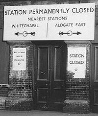 THEME PARTY : List of former and unopened London Underground stations (A narrow wooden door between two brick buttresses. A large sign above saying Station Permanently Closed, Nearest Stations Whitechapel/Aldgate East. Arrows point left and right to each of the two stations named.)