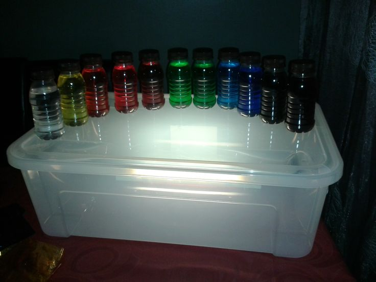 Ampolles de colors amb aigua i colorant sobre calaix de llum.