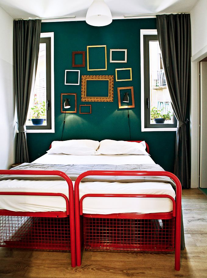Dark green bedroom with frames on wall and red bed post