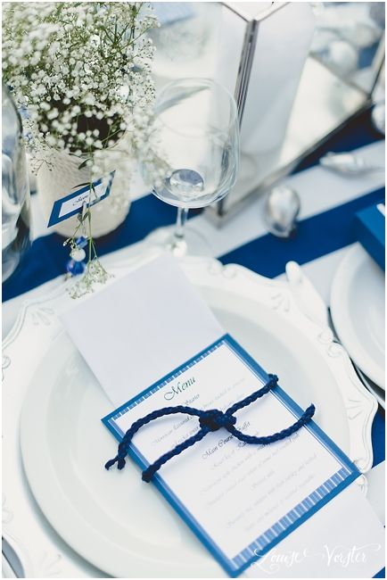 Blue and white menu on folded white napkin with a blue rope tie on a silver under plate.