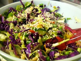 Amy's Nutritarian Kitchen: Kitty's Asian Slaw  1/3 c fresh apple juice 1 T honey 1/4 c rice vinegar 1 1/2 T sesame oil 1 t minced fresh ginger, more to taste 2 t soy sauce  Slaw: 4 c green cabbage, thinly sliced 2 c red cabbage, thinly sliced 2/3 c green onions, thinly sliced 3/4 c thawed frozen green peas 1 large red bell pepper, thinly sliced 1/2 c roasted unsalted peanuts 1/2 to 1 cucumber, sliced and quartered 2 T sesame seeds  Directions: Whisk dressing ingredients in a medium sized…
