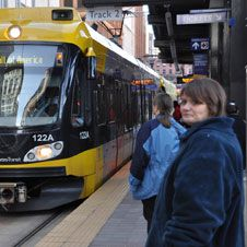 photo of a woman waiting at a light rail stop