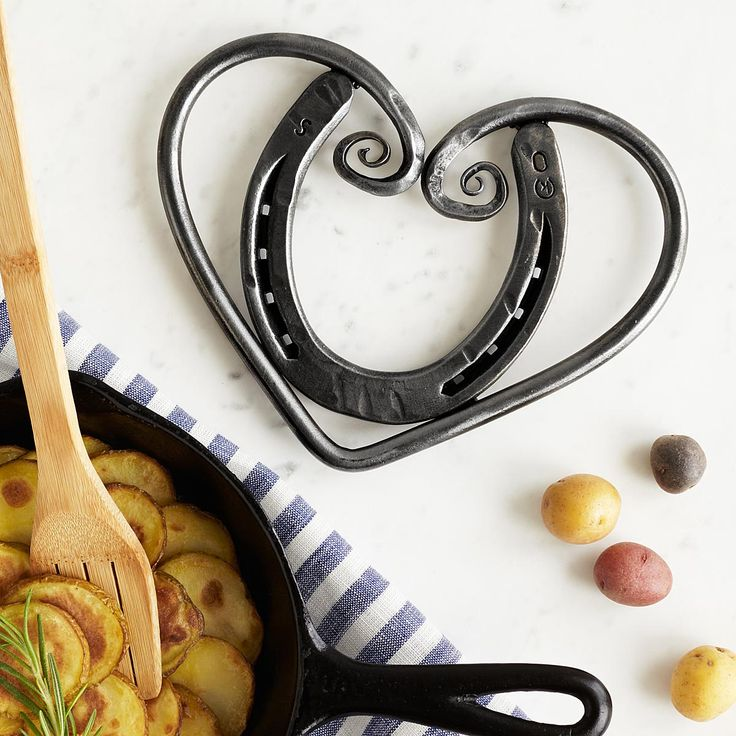 This rustic trivet features a metal horseshoe embraced by a swirling heart of hand-hammered steel.