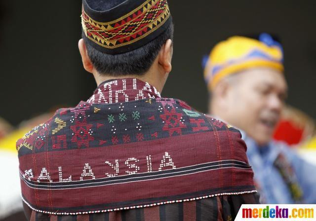 """Seorang warga Malaysia dari suku Mandailing memakai ulos bertuliskan """"Malaysia"""", saat berbicara dengan wartawan."""