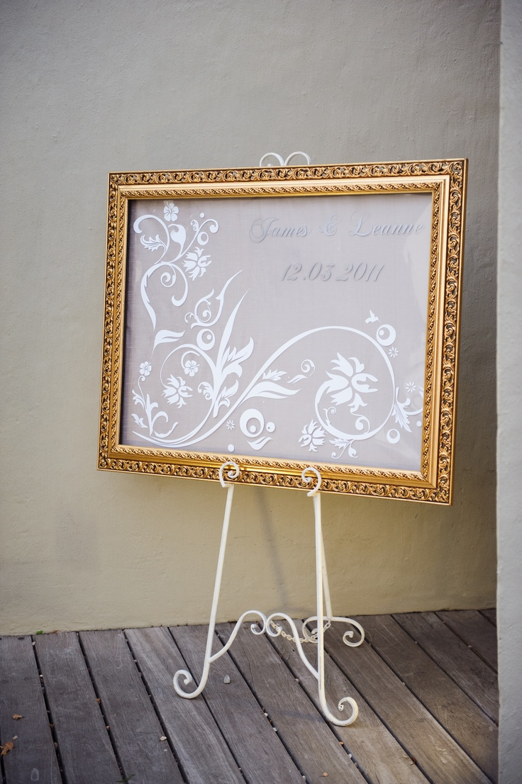 Welcome board:  We ordered the name and pattern decals and stuck them to a piece of glass which we then put in a frame with fabric backing #wedding