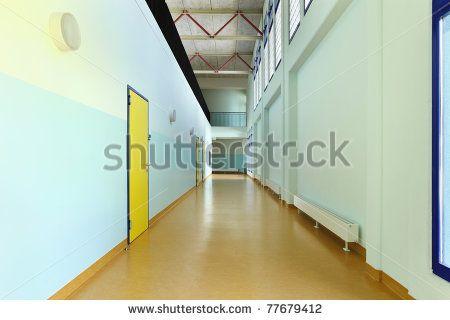 public school, long corridor with yellow door - stock photo
