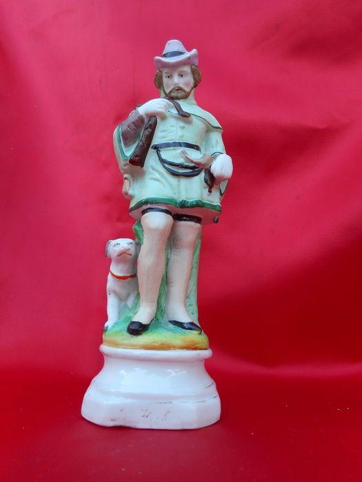 """oud Andenne porseleinen/biscuit___ religieus heilig beeld van St Hubertus (Saint Hubert) 19e eeuws  Zeer zeldzaam beeld van de Heilige Hubertus patroonheilige van de jagers. Mooi met de hand beschilderde gekleurde biscuit/ porselein makelij Andenne (vieux Bruxelles) 19e eeuws  ca 1880.H maximum = 155 cm B x L = 45 x 55 cm mooie staat  met porseleinen voet waarop vaag """"st hubert"""" te lezen staat . Voorstelling: Hubertus in jacht uitrusting  jagershoed  jagerslaarzen kruisboog tegen z'n borst…"""