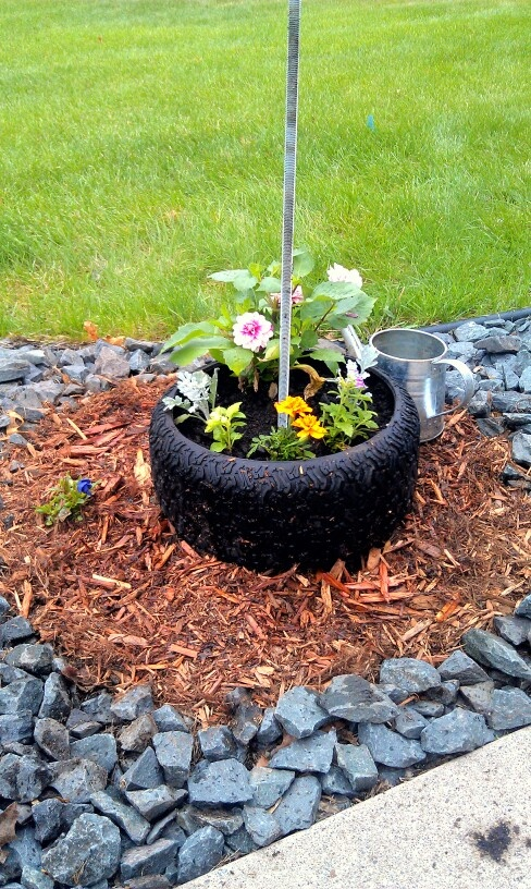 Repurposed lawn mower tire flower pot at the base of my for Car tire flower planter