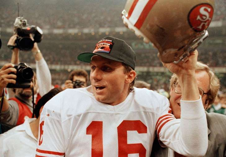 San Francisco 49ers quarterback Joe Montana raises his helmet toward the crowd as he leaves the field following the team's 55-10 victory over the Denver Broncos in the Super Bowl in New Orleans, La., Jan. 28, 1990.