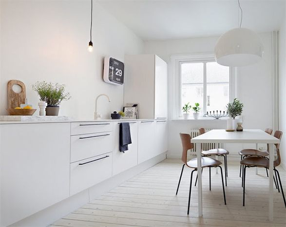 White kitchen with wooden chairs, a white cupola pendant light and white floors