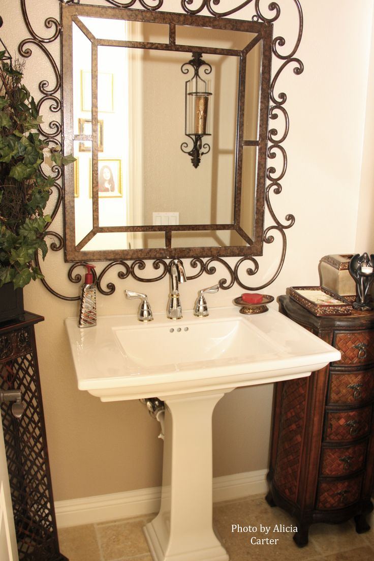 a rustic lamp iron mirror paired with a pedestal sink and chrome faucet is one way to update your small bathroom