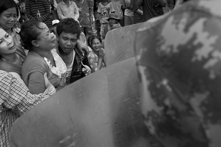 CAMBODIA. Phnom Penh. 16/09/2011: Inhabitants confronting riot police during eviction of Boeung Kak Lake houses not included in the 12,44Ha granted by Prime Minister Hun Sen to some 750 families for an on-site relocation. Shukaku Inc. development company was granted a 99 year lease on the 144Ha on the Boeung Kak lake, filled it with sand and evicted some 3000 families.