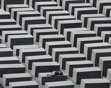 A girl rests on a concrete column of the Holocaust memorial in Berlin, June 17, 2011. The memorial to the murdered Jews of Europe consists of 2,711 charcoal-grey rectangular pillars, which rise from the ground and form a tight grid through which visitors can wander. REUTERS/Tobias Schwarz (GERMANY - Tags: CITYSCAPE RELIGION SOCIETY)