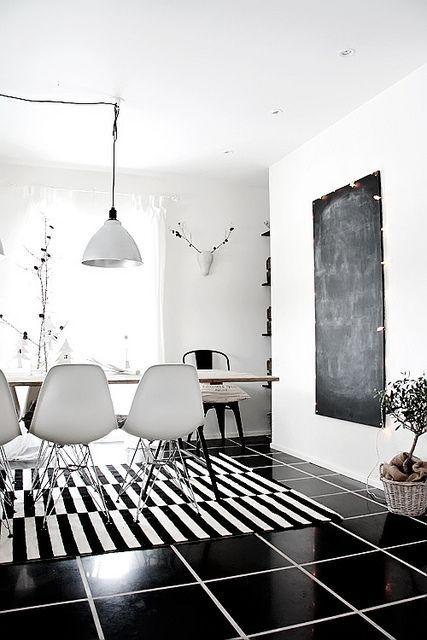 Tapete preto e branco. Luminária pendente industrial. Parede lousa. Cadeiras eames.