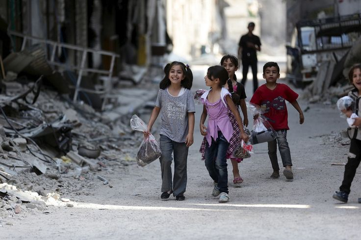 Innocents in time of war: Children carry bags of new clothes ahead of the Eid al-Fitr holiday marking the end of Ramadan in Jobar on July 15, 2015. Bassam Khabieh for Reuters.