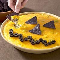 Jack-O-Lantern Layered Mexican Dip - serve with tortilla chips at your Halloween