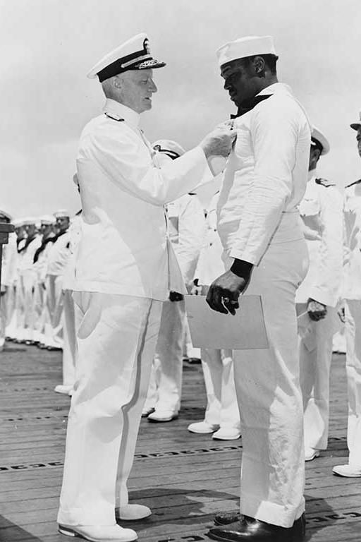 "Nimitz, pins the Navy Cross on Doris Miller, Steward's Mate 1/c, who was cited for ""distinguished devotion to duty, extraordinary courage and disregard of his personal safety during the attack on the Fleet in Pearl Harbor on 7 December 1941. While at the side of his Captain on the bridge, Miller despite enemy strafing and bombing, and in the face of serious fire, assisted in moving his Captain, who had been mortally wounded, to a place of greater safety and later manned and operated a…"