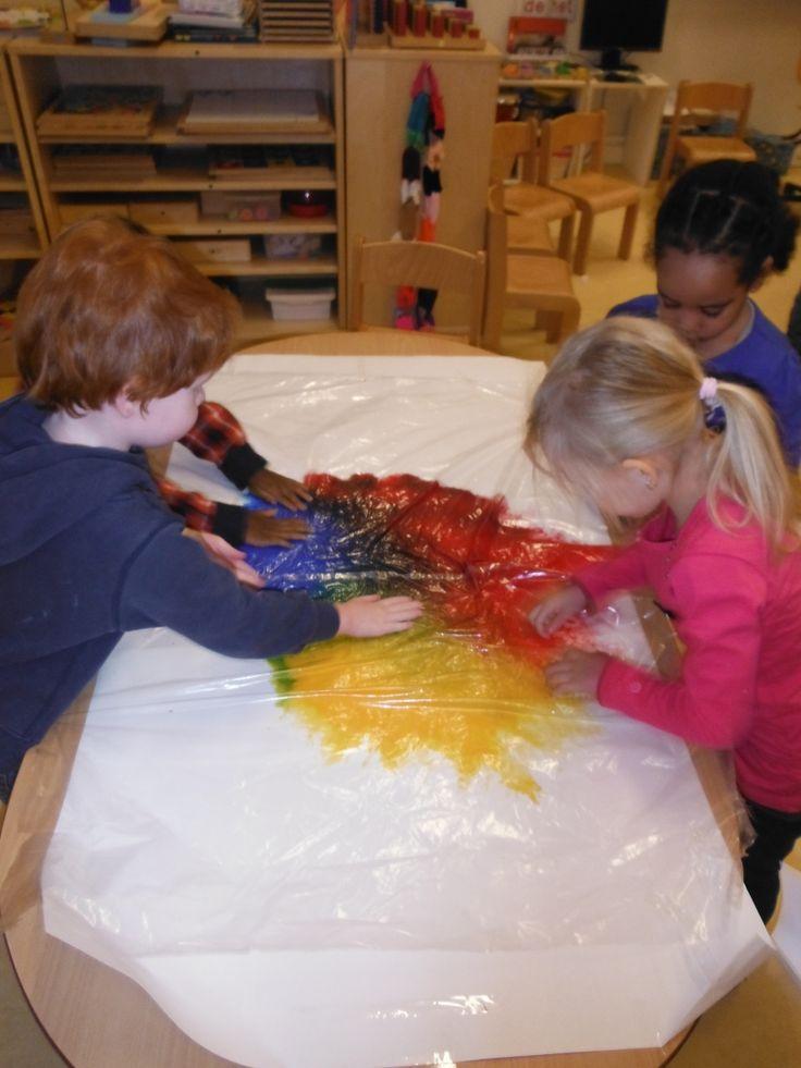 Je plakt een groot vel wit papier op de tafel. Daar doe je dan dotjes verf op van verschillende kleuren. Dan plak je er een plastiek over dat zeker groot genoeg is. Zo dan kunnen ze beginnen met er op te vegen en te schilderen met hun handen. Op het einde doe je de plastic eraf en je hebt een mooi schilderij