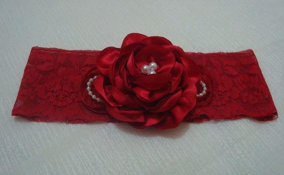 Faixa em renda vermelha com elastano, com flor em cetim e detalhes de pérolas, fios de pérolas e fita. A circunferência da faixa mede 36 cm. R$ 14,90