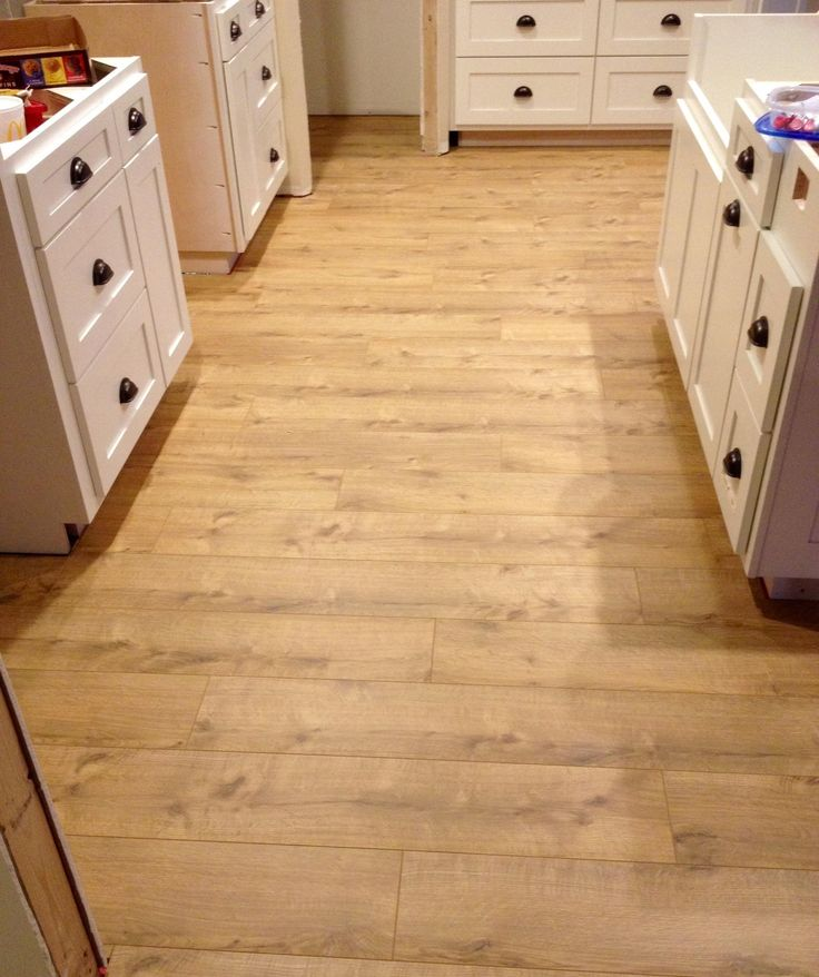 A realistic wood look gives this white kitchen a rustic for Hardwood floors calgary