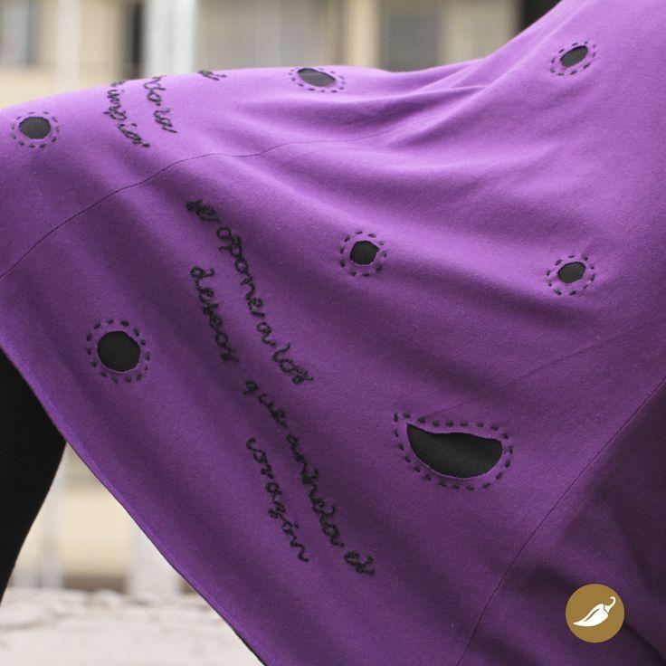 """Falda de algodón bordada y calada inspirada en Violeta Parra. En la prenda se distinguen los versos bordados a mano de la canción: """"Qué pena siente el alma"""": """"Qué pena siente el alma cuando la muerte impía se opone a los deseos que anhela el corazón"""" AndeanHands confeccionó la falda, creando dos capas de tela. Una de las cuales se asoma a través de las figuras caladas que acompañan los versos de una de las canciones más bellas de la creadora.  Autor:Andeanhands Mater..."""