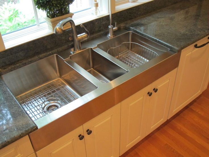 Interesting symmetrical sink design for a larger kitchen. The small middle sink has the garbage disposal--therefore keeping it away from your food prep sink and dish washing sink.