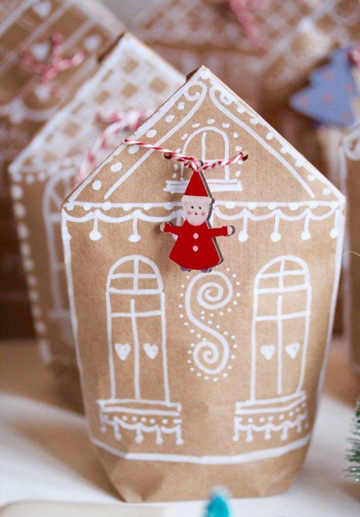 """1. Készíts egy ajándékzacskót (tutorial a blogomon) natúr színű csomagolópapírból. 2. A tetejét tető alakban hajtsd be. 3. Rajzold meg fehér tollal a """"mézeskalács házikó"""" mintáját."""