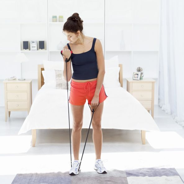 Woman working out with exercise bands in her bedroom