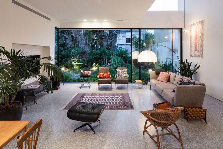 Decoração moderna com portas de vidro, sofá cinza, tapetes, plantas, mesa de madeira e iluminação indireta.