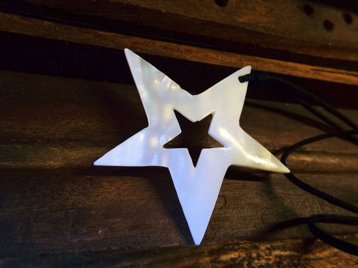 Handmade Abalone seashell star pendant with shimmering effects.