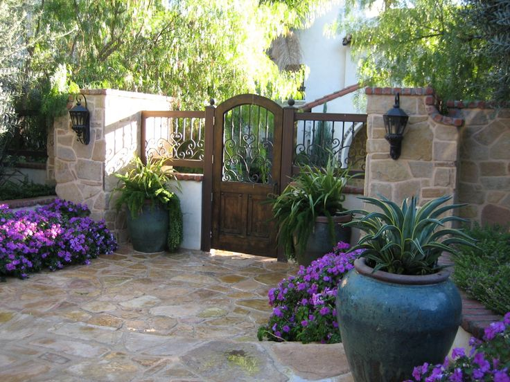 Spanish style stacked stone entry pillars with wrought for Front yard courtyard