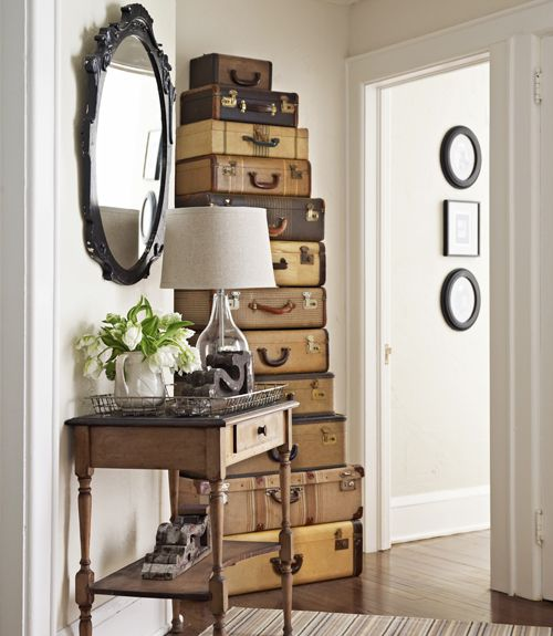 """Put your closet in plain sight by stacking vintage luggage to add a decorative yet practical oomph to your hallway. The """"drawers"""" will provide storage for out-of-season pieces."""